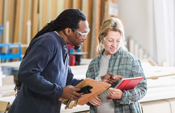 Two people in wood mill using Paylocity Payroll software on a tablet.