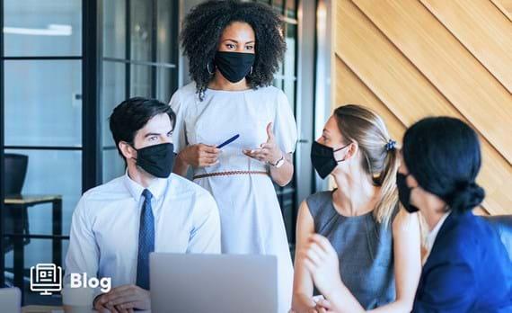 Group of individual's wearing masks looking at computer screen