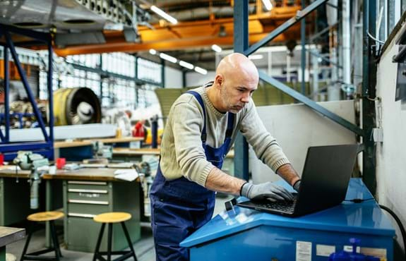 Man in manufacturing plant using Paylocity software