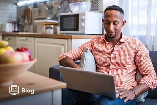 Man in orange checkered shirt sitting in kitchen smiling while looking at computer.